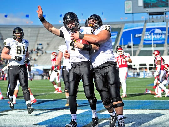 Vanderbilt quarterback Patton Robinette (4) is congratulated by offensive linesman Jake Bernstein (53)  after scoring a touchdown against Houston in the first quarter during the 2014 BBVA Compass Bowl at Legion Field in Birmingham, Ala., Saturday, Jan. 4, 2014.