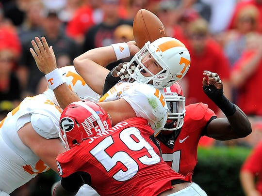 Tennessee quarterback Nathan Peterman (12) is sacked by Georgia outside linebacker Jordan Jenkins (59) as the University of Tennessee plays Georgia in Sanford Stadium  Saturday Sept. 27, 2014, in Athens, GA.