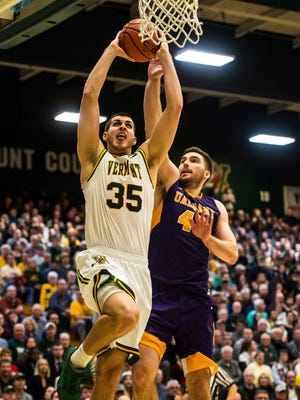 UVM's Payton Henson takes off past Albany's Greig Stire for the dunk during their men's college basketball game at Patrick Gym on Jan. 24. UVM won, 61-50.