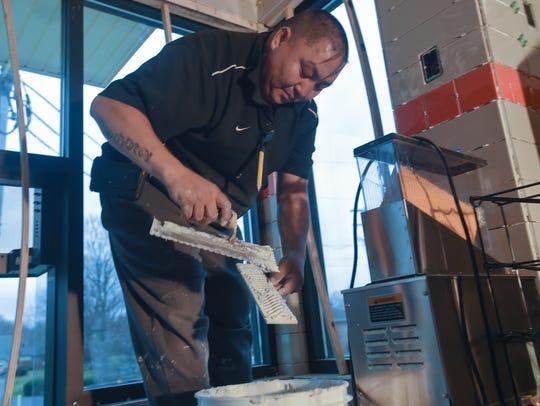 Gambat Torloo places glue on a tile inside Dunkin'