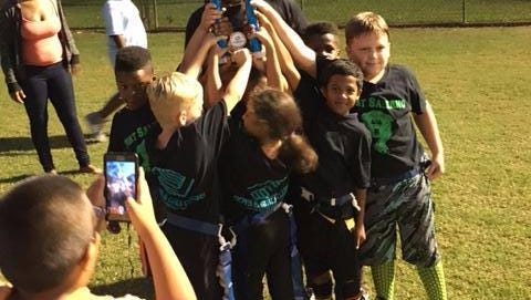 Coach Joshua Perry leads his 6- to 8-year-old flag football team to a season victory. He and the other Boys & Girls Clubs coaches strive to teach their players teamwork and sportsmanship.
