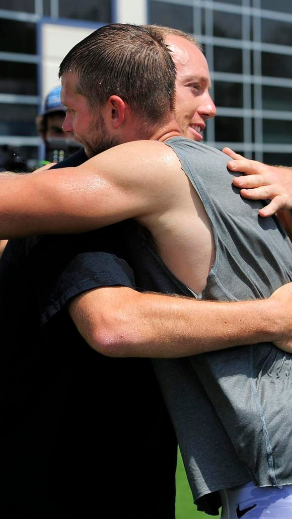 Former Titans linebacker Tim Shaw hugs quarterback Jake Locker after the team took the ALS ice bucket challenge in Shaw's honor.