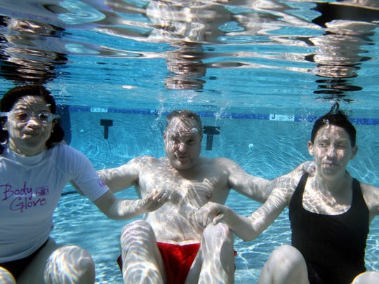 From left,  Christie Johnson, swim instructor Jeff Krieger, and Katherine Ellsworth  go under water in the pool at the Saw Mill River Club in Mount Kisco.