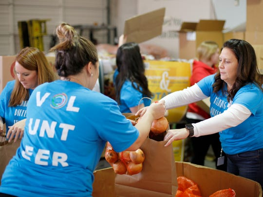 Volunteers pack onions into bags at the FreeStore Foodbank in the Over-the-Rhine neighborhood of Cincinnati on Wednesday, Dec. 20, 2017. Volunteers gathered Wednesday morning to pass out food for holiday season meals to those in need.