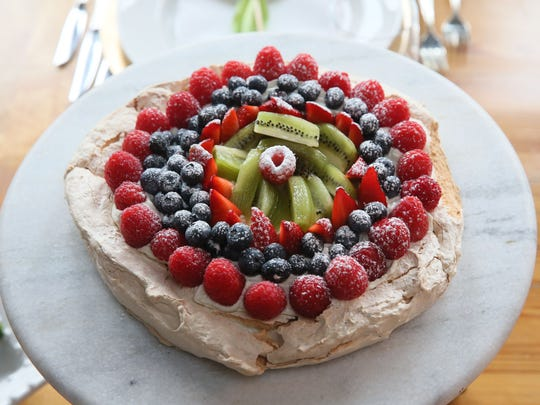 A whipped cream- and fruit-topped pavlova makes an