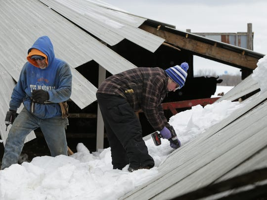 Jennifer and John Yost III take apart their barn roof, which collapsed under last weekend's heavy snow. Several cows were in the section that collapsed and had to be rescued.