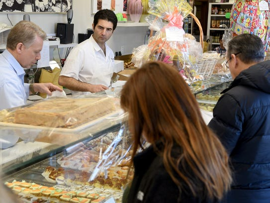 Giancarlo Palazzone, on left, grew up in Italy and owns Palazzone 1960 in Wayne. Palazzone helps customers at his store on a busy Sunday morning. Palazzone sells over 10,000 St. Joseph's Day zeppole to customers celebrating the day, this year on March 19, 2018.