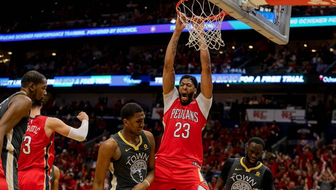 May 4: Anthony Davis dunks over Draymond Green and Kevon Looney during Game 3.