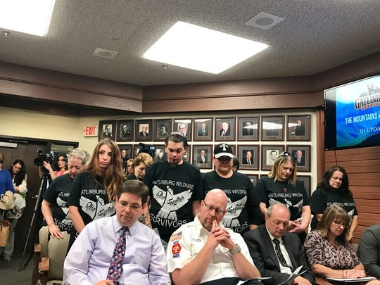 Members of the Gatlinburg Wildfire Survivors bow their heads for a moment of silence to remember fire victims during a Gatlinburg City Commission meeting May 9, 2017.