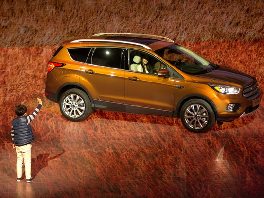 A child waves as the latest model of the Ford Kuga