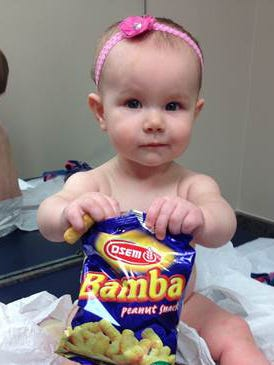 Estelle holds a bag of peanut snacks in her pediatrician's office at age nine-months, in Columbus, Ohio.