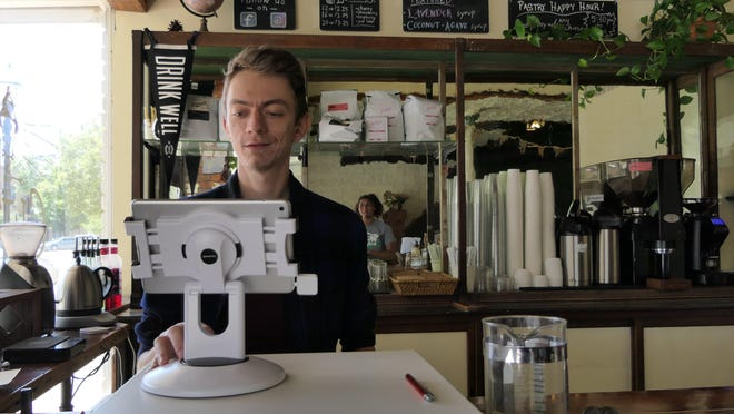Wes Meadows, the barista at Clive's Staples coffee shop and bakery in Sterling, Kansas waits on a customer.