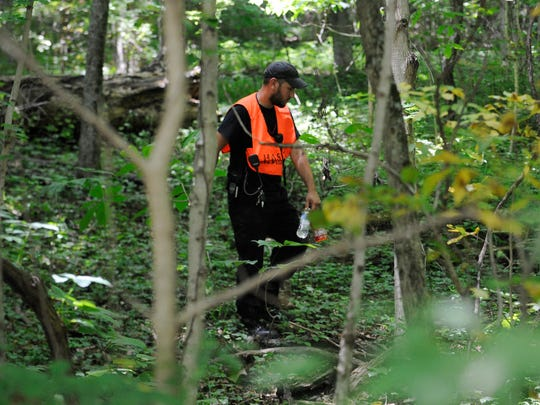 A Ross County Search and Rescue team member searches Monday, June 22, 2015, near the area where Tiffany Sayre's body was found on Cave Road.