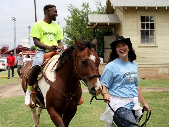 Markeis Lee rides Apache lead by his owner Hannah Daniel
