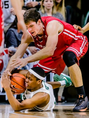 Cassius Winston ,bottom, of MSU rips the ball away from Ethan Happ of Wisconsin to secure a defensive rebound late in the 2nd half of their game Sunday February 26, 2017 in East Lansing.  KEVIN W. FOWLER PHOTO