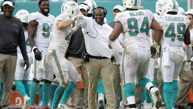 Miami Dolphins head coach Brian Flores celebrates with the defense after the Dolphins forced a safety against the New York Jets.