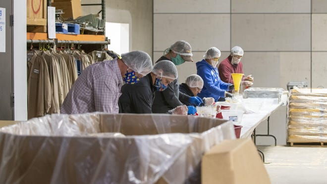 """Hutton Construction is paying employees to pack meals for """"The Outreach Program,"""" a charity that distributes meals to those suffering from food insecurity, in a first-of-its-kind program during the COVID-19 pandemic."""