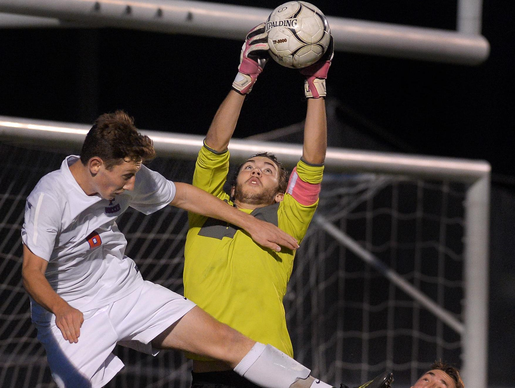 Hilton goalie Jesse DePrez, center, reaches for the ball between Fairport's Nick Guida, left, and Pete Critchlow during a regular season game at Fairport High School on Wednesday. The teams played to a 3-3 draw.