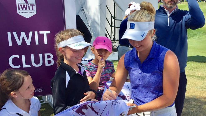 Erica Shepherd (right) signs autographs for some young fans.