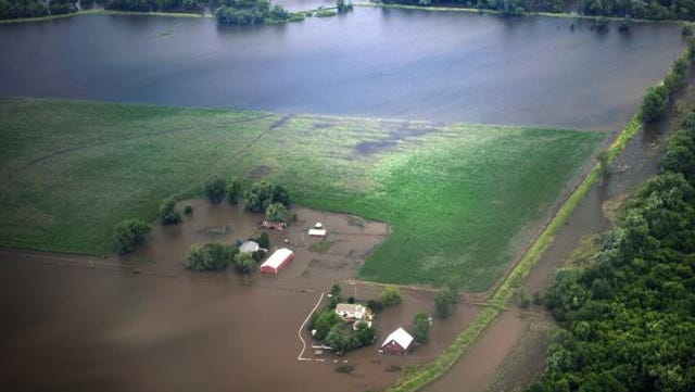 An aerial view of a flooded Midwestern farm has been all too common during four severe floods that have affected the region since 2008.