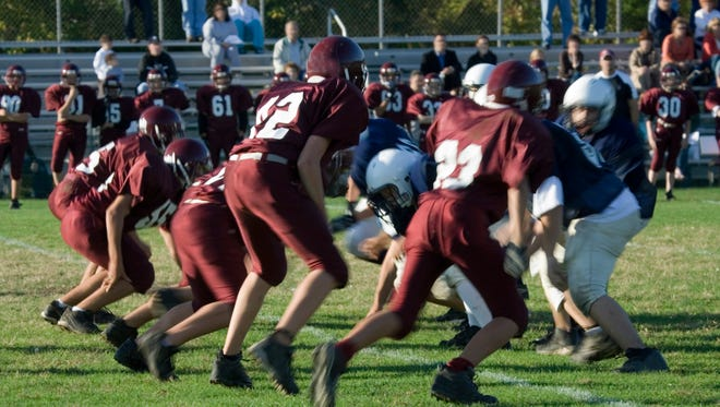 Young men playing high school football on an afternoon in October.