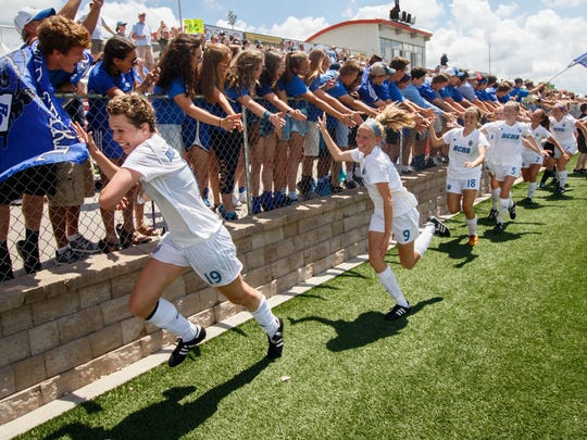 Brookfield Central junior Jenny Cape (left) leads teammates past jubilant fans after winning the WIAA Division 1 state soccer championship against Bay Port at Uihlein Soccer Park in Milwaukee on Saturday, June 17, 2017.