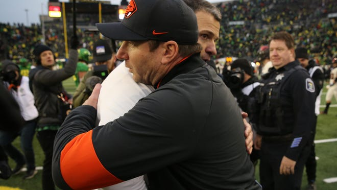 Oregon coach Mario Cristobal, left. and Oregon State coach Jonathan Smith embrace at midfield after the 123rd Civil War football game.