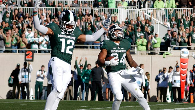 Michigan State Spartans RB Gerald Holmes, right, and WR R.J. Shelton celebrate a touchdown on Saturday, Oct. 8, 2016, in East Lansing.