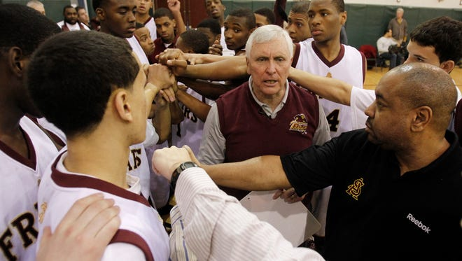 Bob Hurley, center, head coach of the St. Anthony High School boys' basketball team, huddles with his team during a game in Jersey City.