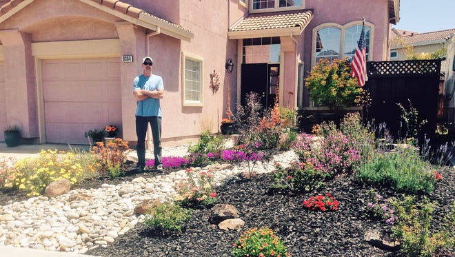 In this photo provided by Karen Jenkins, her husband, Rick Jenkins, poses for a photo in the front yard at their home in Gilroy, Calif., Wednesday, May 27, 2015. A major water wholesaler on Tuesday added $350 million to its budget to replenish a cash-for-grass program that has gained popularity during the California drought with homeowners, landlords and businesses looking to replace water-draining lawns. Jenkins took advantage of the rebate program last year and replaced his lawn with a dry, rocky river bed. (AP Photo/Karen Jenkins)