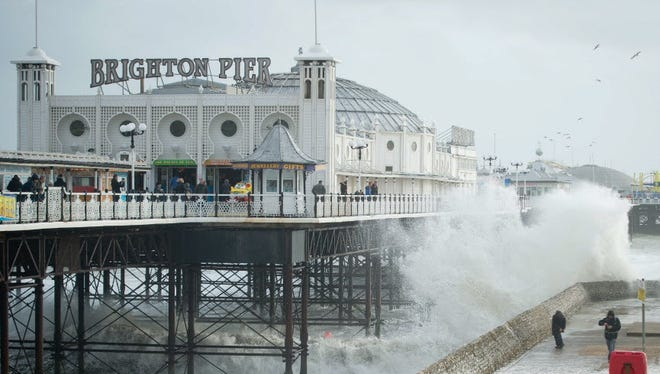 People look on as large waves crash against the walls of Brighton seafront, in southern England on October 27, 2013.