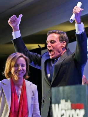 Sen. Mark Warner, D-Va., gives a thumbs up as he arrives on stage with his wife, Lisa Collis during an election party in Arlington, Va., Wednesday, Nov. 5, 2014. Warner is locked in a tight race with Republican Ed Gillespie. (AP Photo/Steve Helber)