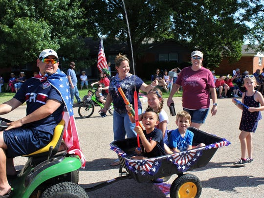 Sebastian Garcia, 8, launches water toward parade watchers while his dad, Patrick (aka Flag Man), drives.The wagon was full of water, providing both ammunition and a cooling effect for last year's Hillcrest Neighborhood Parade.