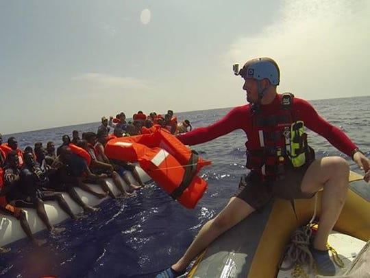 A volunteer works to distribute life jackets to refugees off the coast of Libya.