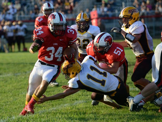 Liberty Union's Braden Powers runs the ball during the Lions season opener Friday night, Aug. 29, 2014, against Berne Union. The Lions won the home game 60-0.