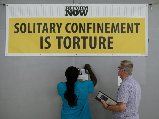 Talib Akbar (left) and Ed Winney put up information about solitary confinement Saturday on the side of a replica solitary confinement cell being displayed this week at the West Side Moravian Church in Green Bay.