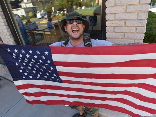 Byron Berrocal hols an American flag as protesters