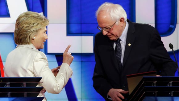 Hillary Clinton gestures toward Bernie Sanders at the