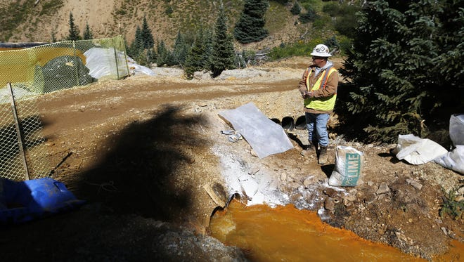"FILE - In this Aug. 14, 2015 file photo, an Environmental Protection Agency contractor keeps a bag of lime on hand to correct the PH of mine wastewater flowing into a series of sediment retention ponds, part of danger mitigation in the aftermath of the blowout at the site of the Gold King Mine outside Silverton, Colo. Congressional Republicans on Thursday, Oct. 29, 2015, revived ""Good Samaritan"" legislation designed to encourage companies and nonprofits to clean up abandoned mines by protecting them from liability for environmental accidents in the future. (AP Photo/Brennan Linsley, file)"