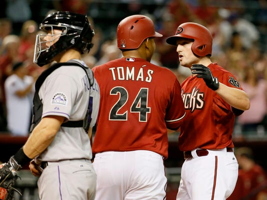 Arizona Diamondbacks Jordan Pacheco, right, is greeted at home plate by Yasmany Tomas after hitting a three-run home run as Colorado Rockies catcher Nick Hundley looks away during the fifth inning of a baseball game, Wednesday, April 29, 2015, in Phoenix. (AP Photo/Matt York)