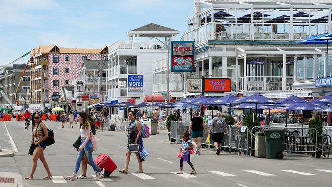 Daytime beachgoers including families and friends spend a summer day at Hampton Beach.
