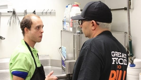 Undercover Boss Nader Masadeh talking with a worker in a Buffalo Wings and Rings restaurant. The episode of CBS' Undercover Boss that includes Nasadeh airs Sunday night.