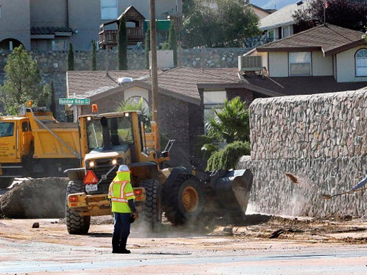 "A crew from the city transportation department collects dirt at Redd Road and Bear Ridge Drive on Monday in West El Paso. Storms on Friday caused flooding, power outages and property damage primarily in West and Northeast El Paso. El Paso Water Utilities announced the ""Turn Around Don't Drown"" safety campaign Monday to help El Pasoans deal with the dangers of flooding."