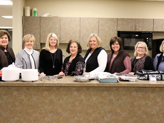 Sandra Marbury, Amanda Kirkbride, Mary Beth Deloach, Pam McCarty, Jan Thompson, Elizabeth Johnson and Kay Forsythe pose for a picture with Emily Crabtree (second from left), former principal of Pope Elementary School, before dinner was served during a reunion held Feb. 16, 2018, at the First United Methodist Church Activity Center in downtown Jackson.