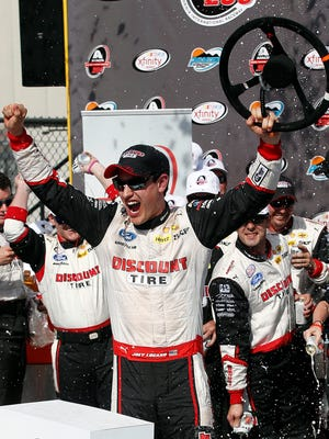 Joey Logano celebrates in victory lane after winning the NASCAR Xfinity Series auto race on Saturday, March 14, 2015, in Avondale, Ariz.