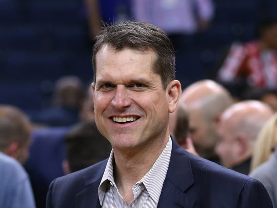 Michigan football coach Jim Harbaugh stands on the court after a game between the Golden State Warriors and the Oklahoma City Thunder at Oracle Arena.