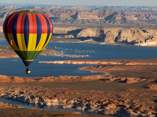 A hot air balloon participating in the 13th annual Page Lake Powell Hot Air Balloon Regatta floats in the skies above Page with Lake Powell and Wahweap Marina in the background Sunday, Nov. 8, 2015. A weekend filled with fantastic ballooning weather saw 60 hot air balloons filling the skies over Lake Powell on Friday, Saturday and Sunday mornings. In additions, about 20 of the balloons were lined up along Lake Powell Boulevard Saturday night for a balloon glow and street festival.
