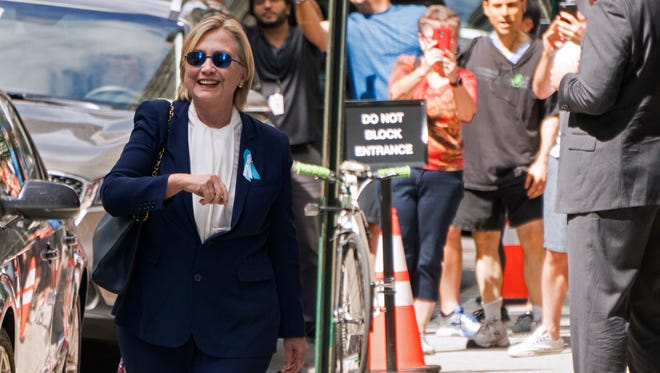 """Democratic presidential candidate Hillary Clinton walks from from her daughter's apartment building Sunday, Sept. 11, 2016, in New York. Clinton unexpectedly left Sunday's 9/11 anniversary ceremony in New York after feeling """"overheated,"""" according to her campaign."""