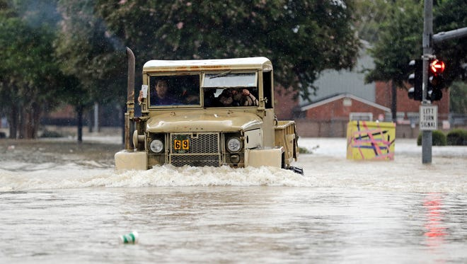 A truck pushes through floodwaters from Tropical Storm Harvey on Sunday.