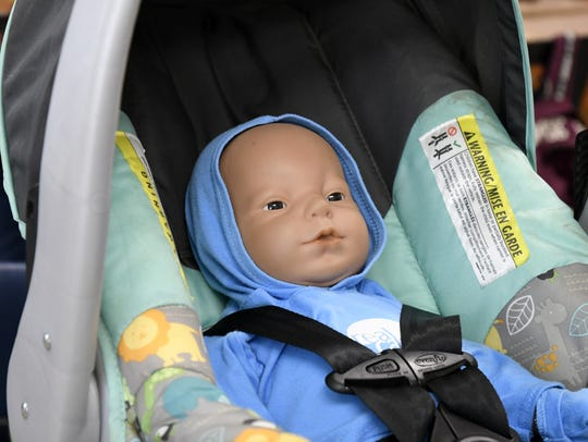 A student's electronic baby sits in a provided car